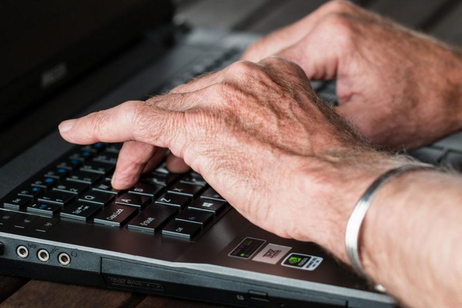 Alte Hände auf einer Tastatur